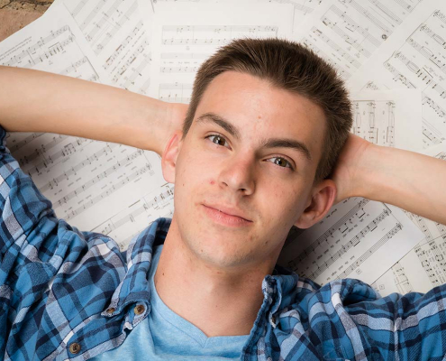 senior portraits boy with music sheets behind his head